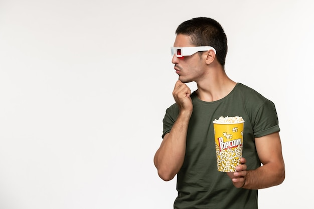 Vorderansicht junger mann im grünen t-shirt, das popcorn in der d sonnenbrille hält film auf weißem wandfilm einsame kino-männerfilme ansehen