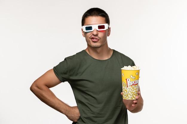 Vorderansicht junger mann im grünen t-shirt, das popcorn-paket in d sonnenbrille auf dem weißen wandfilm einsame kino-männerfilme hält