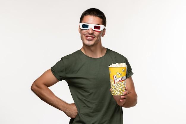 Vorderansicht junger mann im grünen t-shirt, das popcorn-paket in d sonnenbrille auf weißen schreibtischfilm einsamen kino-männerfilmen hält
