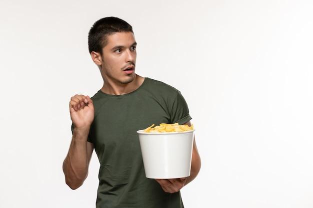Vorderansicht junger mann im grünen t-shirt mit kartoffel-cips, die film auf hellweißem wandfilm person männlich einsames filmkino ansehen