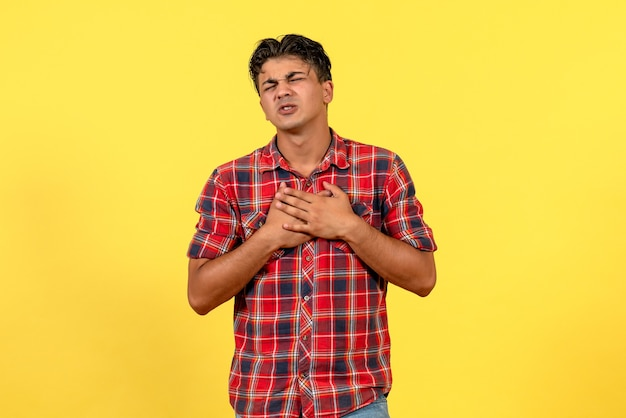 Vorderansicht junger mann im hellen hemd, das auf männlicher modellfarbe des gelben hintergrunds aufwirft