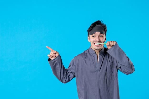 Vorderansicht junger mann im pyjama, der seine zähne auf blauem hintergrund putzt farbe ruhe nacht wecken alptraum menschliches bett dunkles kissen