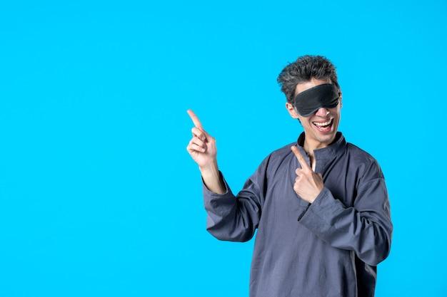 Vorderansicht junger mann im pyjama und schlafverband auf blauem hintergrund farbe ruhe alptraum schlaf dunkle schlafzimmer träume bett nacht