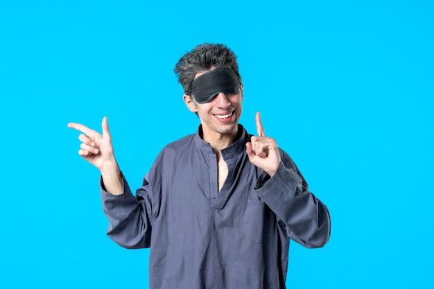 Vorderansicht junger mann im pyjama und schlafverband auf blauem hintergrund farbe ruhe nacht albtraum schlaf dunkle schlafzimmer träume bett