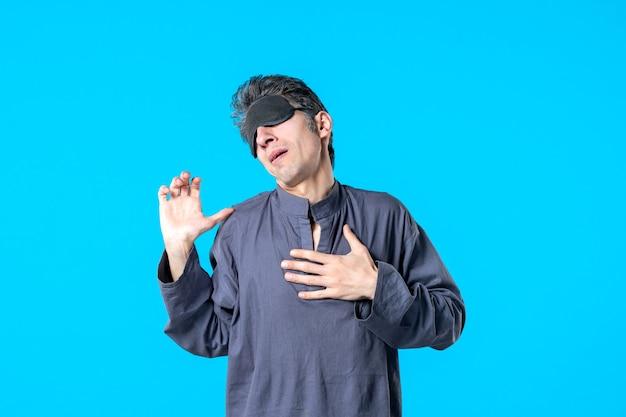Vorderansicht junger mann im pyjama und schlafverband auf blauem hintergrund ruhe dunkles schlafzimmer albtraum schlaf nacht farbbett träume