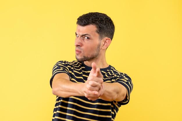 Vorderansicht junger mann im schwarz-weiß gestreiften t-shirt, das fingerpistole zur kamera auf gelbem lokalisiertem hintergrund setzt