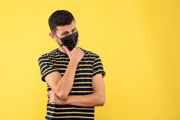Vorderansicht junger mann im schwarz-weiß gestreiften t-shirt, das hand auf seinem kinngelben hintergrund setzt