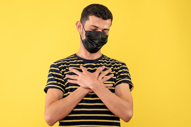 Vorderansicht junger mann im schwarz-weiß gestreiften t-shirt, das hand auf seiner brust auf gelbem hintergrund setzt