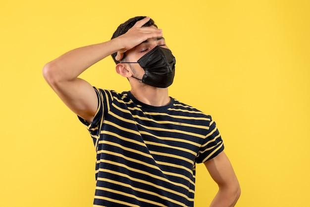 Vorderansicht junger mann im schwarz-weiß gestreiften t-shirt, das hand auf seiner stirn auf gelbem hintergrund setzt