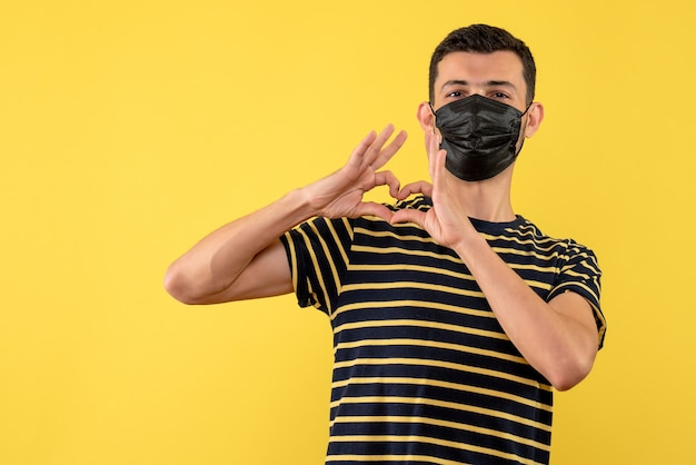 Vorderansicht junger mann im schwarz-weiß gestreiften t-shirt, das herzzeichen mit den fingern auf gelbem hintergrund macht