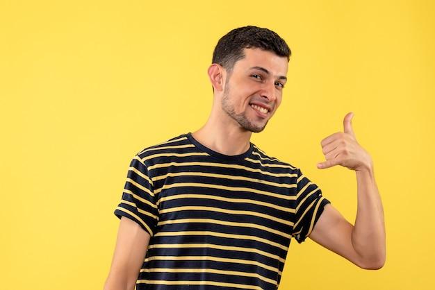 Vorderansicht junger mann im schwarz-weiß gestreiften t-shirt, das mich zeichen auf gelbem lokalisiertem hintergrund anruft