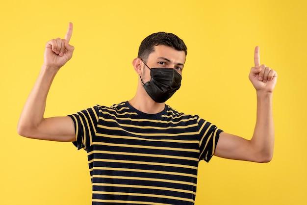 Vorderansicht junger mann im schwarz-weiß gestreiften t-shirt, das mit den fingern oben auf gelbem hintergrund zeigt