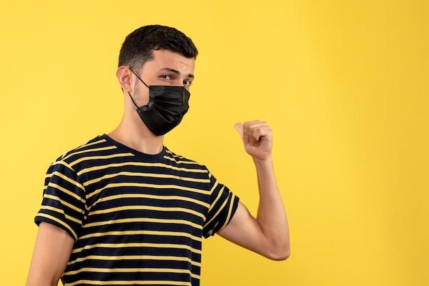 Vorderansicht junger mann im schwarz-weiß gestreiften t-shirt, das mit finger zurück auf gelbem hintergrund zeigt