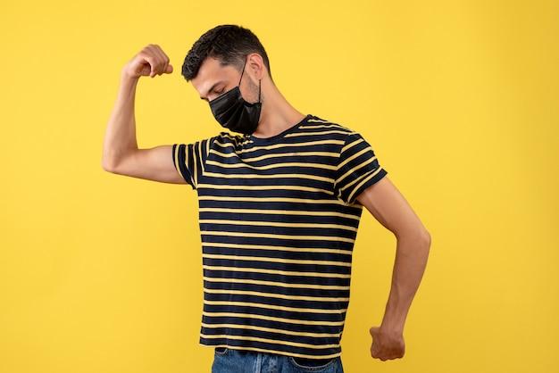 Vorderansicht junger mann im schwarz-weiß gestreiften t-shirt, das muskeln auf gelbem hintergrund zeigt