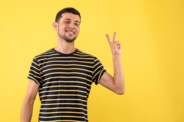 Vorderansicht junger mann im schwarz-weiß gestreiften t-shirt, das siegeszeichen auf gelbem lokalisiertem hintergrund macht