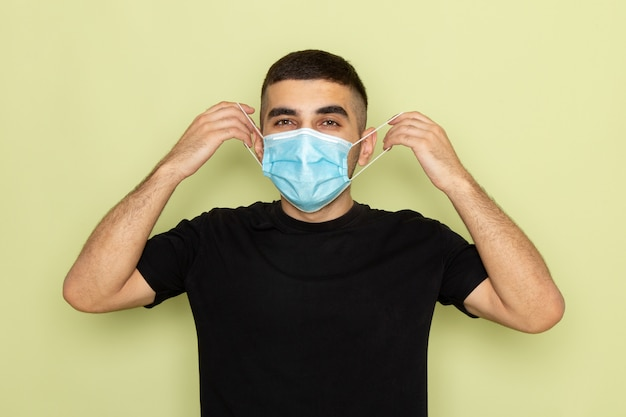 Vorderansicht junger mann im schwarzen t-shirt, das sterile maske auf grün trägt