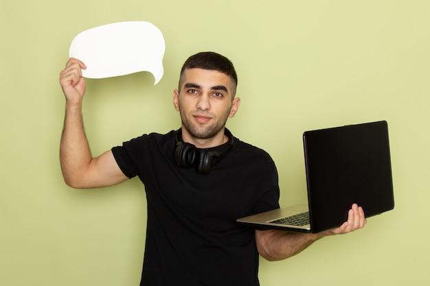 Vorderansicht junger mann im schwarzen t-shirt unter verwendung des laptops, der weißes zeichen auf grün hält
