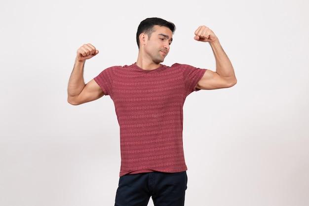 Vorderansicht junger mann im t-shirt posiert und beugt sich auf weißem hintergrund