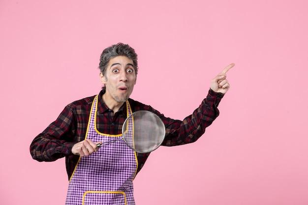 Vorderansicht junger mann im umhang mit sieb auf rosa hintergrund job beruf ehemann küche koch horizontaler lebensmittelarbeiter