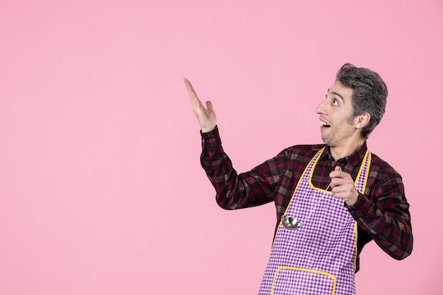 Vorderansicht junger mann im umhang mit silbernem suppenlöffel auf rosa hintergrund küche arbeiter beruf ehemann küche koch essen horizontale farben