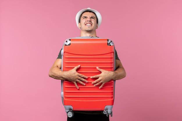 Vorderansicht junger mann im urlaub, der seine große tasche auf rosafarbenem raum trägt