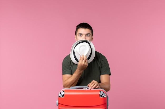 Vorderansicht junger mann im urlaub, der seinen hut auf dem rosa raum hält
