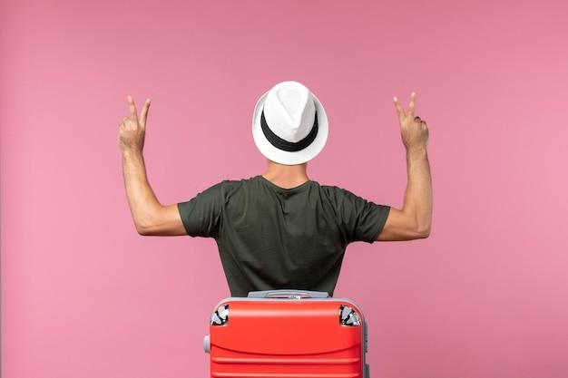 Vorderansicht junger mann im urlaub mit hut auf dem rosa raum