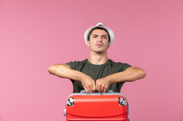 Vorderansicht junger mann im urlaub mit roter tasche auf dem rosa raum
