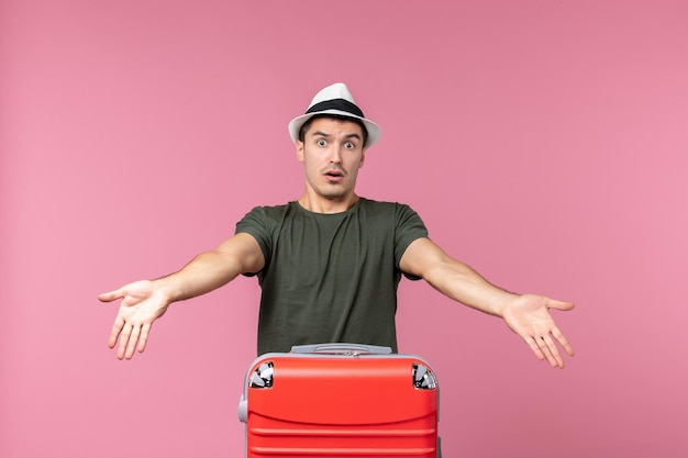 Vorderansicht junger mann im urlaub mit roter tasche auf hellrosa raum