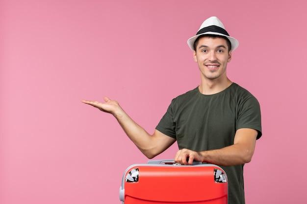 Vorderansicht junger mann im urlaub mit seiner roten tasche auf rosa bodenreise seereisender mann reiseurlaub