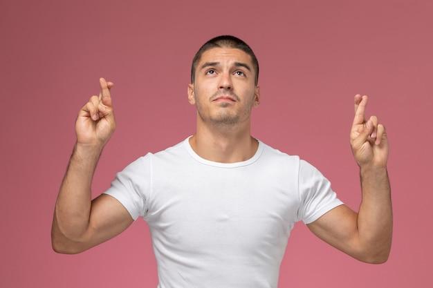 Vorderansicht junger mann im weißen hemd, das mit gekreuzten fingern auf rosa hintergrund aufwirft