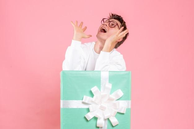 Vorderansicht junger mann im weißen hemd mit geschenk auf dem rosa hintergrund