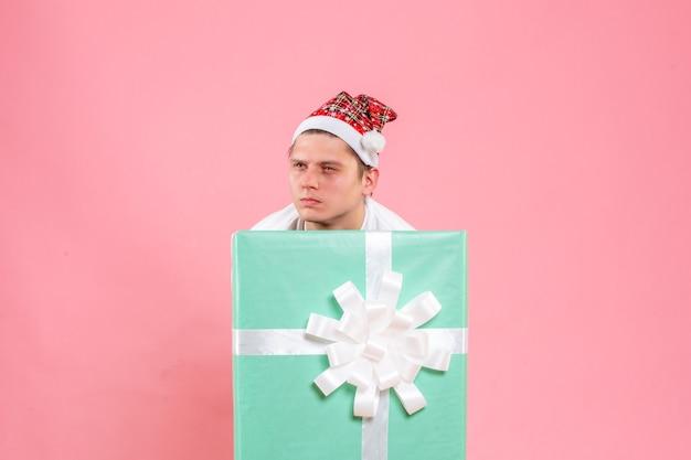 Vorderansicht junger mann im weißen hemd mit geschenk, das auf rosa hintergrund schaut
