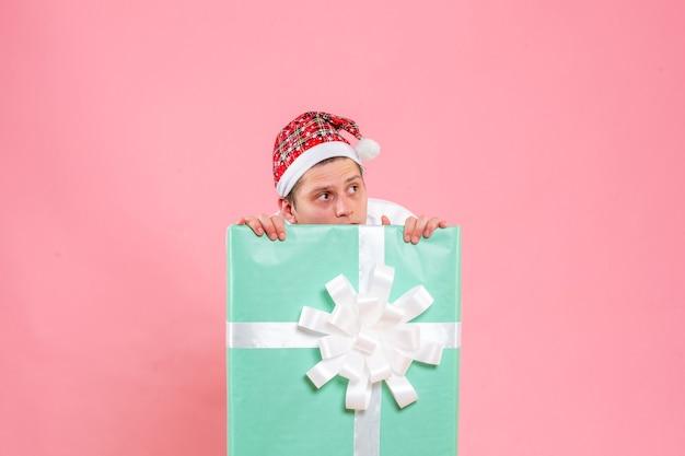 Vorderansicht junger mann im weißen hemd mit geschenk, das auf rosa hintergrund versteckt