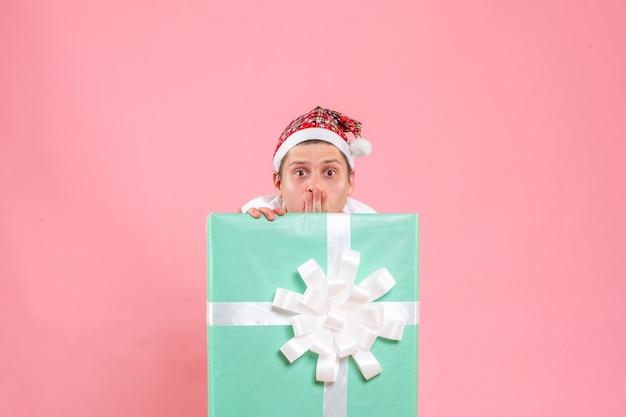 Vorderansicht junger mann im weißen hemd mit geschenk schockiert auf rosa hintergrund