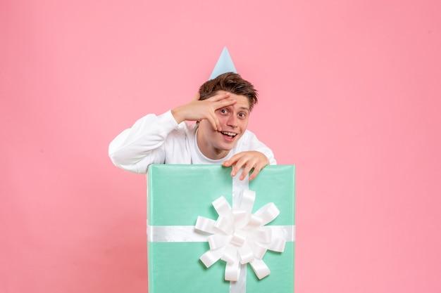 Vorderansicht junger mann im weißen hemd mit kappe und geschenk auf dem rosa hintergrund