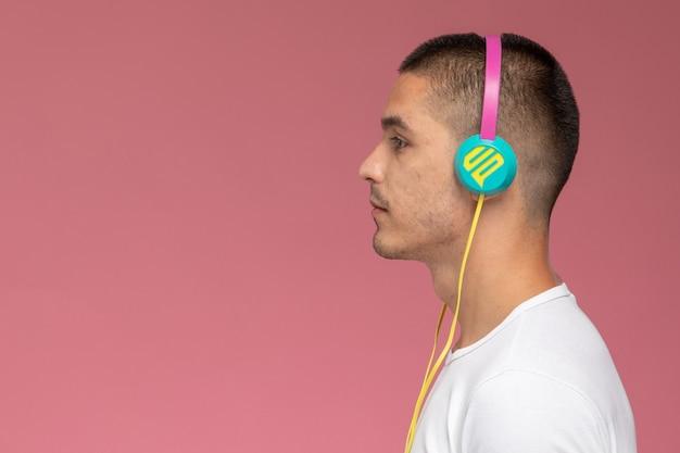 Vorderansicht junger mann im weißen t-shirt, das musik über kopfhörer auf dem hellrosa hintergrund hört