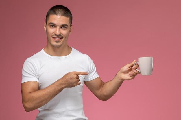 Vorderansicht junger mann im weißen t-shirt, das tasse mit kaffee auf dem rosa hintergrund hält
