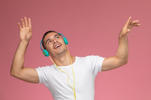 Vorderansicht junger mann im weißen t-shirt tanzt und hört musik über kopfhörer auf rosa schreibtisch