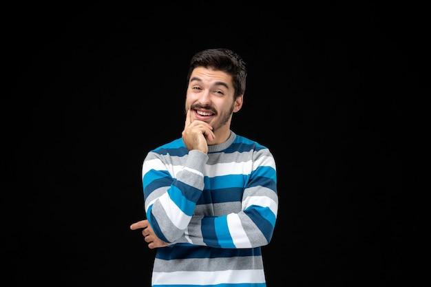 Vorderansicht junger mann in blau gestreiftem jersey, der auf schwarzer wand denkt und lächelt