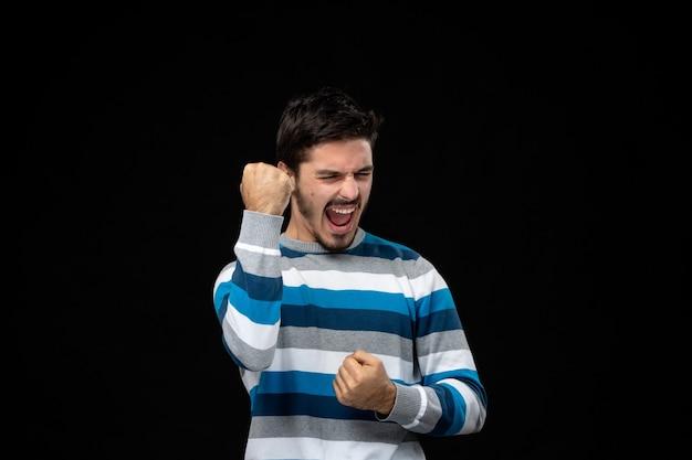 Vorderansicht junger mann in blau gestreiftem trikot, der sich an der schwarzen wand freut