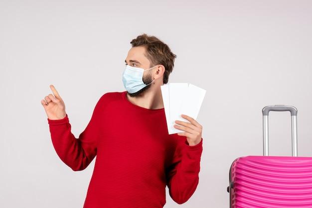 Vorderansicht junger mann in der sterilen maske, die tickets auf weißer wand covid-flugzeug urlaub emotion virus flüge reisefarbe hält