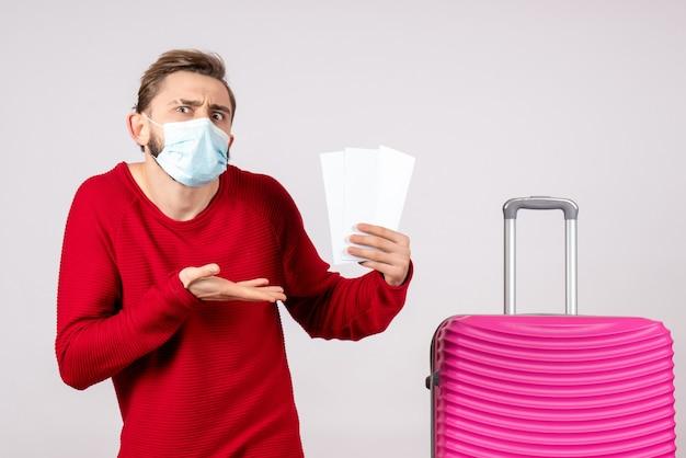 Vorderansicht junger mann in der sterilen maske, die tickets auf weißer wandreise covid-flugreise-urlaubsvirus färbt emotion hält