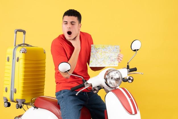 Vorderansicht junger mann in freizeitkleidung auf moped mit reisekarte, die kehle hält