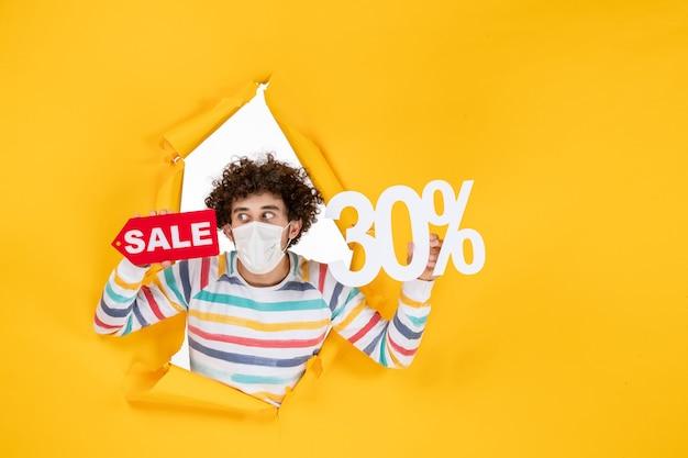 Vorderansicht junger mann in maske, der auf der gelben pandemischen farbe hält, rote gesundheit covid-fotovirus-verkauf einkauft