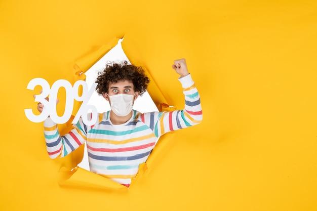 Vorderansicht junger mann in maske, der auf gelbem pandemischem farbeinkaufsgesundheitskovid-fotovirusverkauf hält