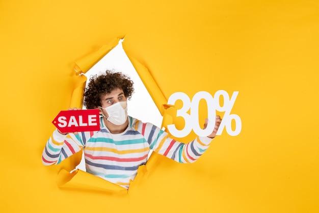 Vorderansicht junger mann in maske, der auf gelben pandemiefarben hält, rote gesundheit covid-fotovirus-verkauf einkaufen