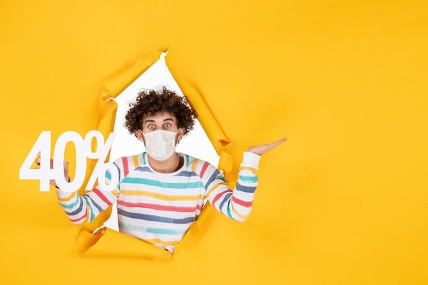 Vorderansicht junger mann in maske, die schrift auf gelben viruspandemie-shopping-gesundheitskovid-fotoverkaufsfarben hält