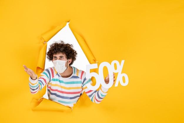 Vorderansicht junger mann in maske mit schrift auf gelbem einkaufsgesundheits-pandemie-kovid-fotos verkauf farbvirus