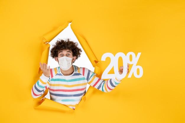 Vorderansicht junger mann in maske mit schrift auf gelbem verkauf coronavirus pandemie gesundheit covid-foto writing